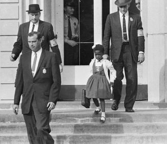 Ruby Bridges being escorted by detectives out of school for her safety.